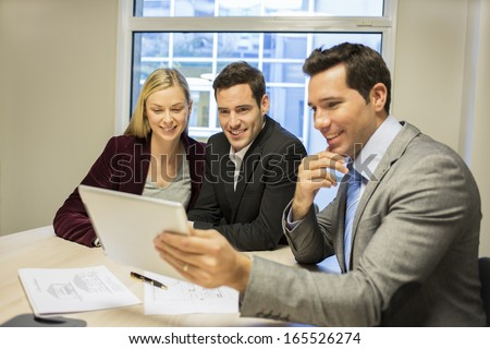 Architect presenting a new project to a smiling young couple  - stock photo