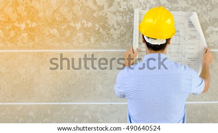 architect reading architectural plans  and concrete wall background,soft light