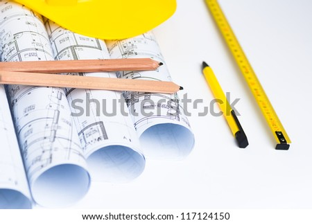 Architect rolls and plans.and yellow helmet - stock photo