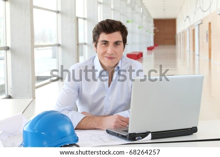 Architect sitting in front of laptop computer - stock photo