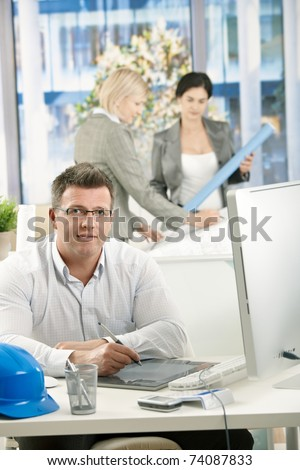 Architect sitting in office, designers working together in background.?
