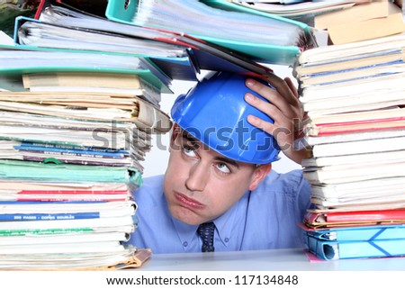 Architect surrounded by piles of paperwork - stock photo