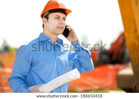 Architect talking at the phone in a construction site
