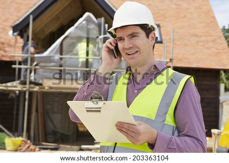 Architect Talking On Mobile Phone At Construction Site - stock photo