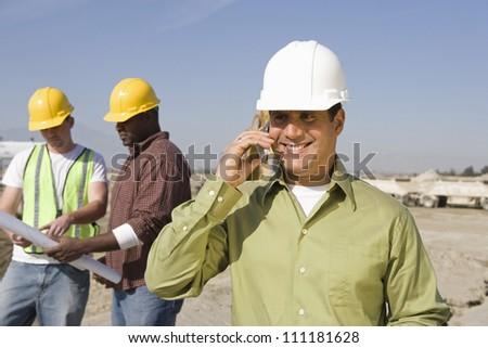 Architect telephoning at construction site - stock photo
