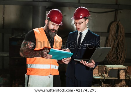 Architect the suit and helmet and foreman Builder in overalls and with a tattoo compare their drawing of a construction project with a work object