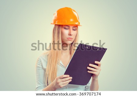 Architect thinking. Closeup portrait serious young construction woman with yellow cap pondering situation planning looking down at notepad isolated green background. Positive emotion facial expression - stock photo