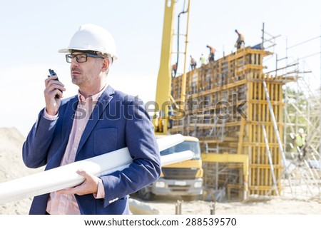 Architect using walkie-talkie while holding blueprints at construction site - stock photo