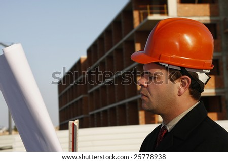 Architect wearing a protective helmet standing in front of a building site.
