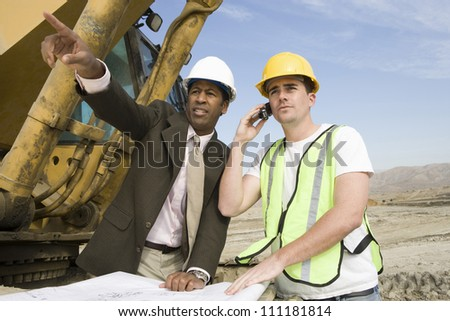 Architect wearing hard hat as he's on call at construction site - stock photo