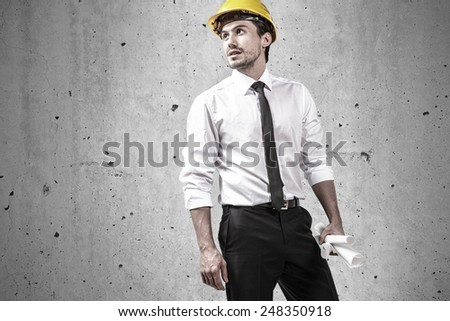 Architect wearing yellow hard hat  holding some plans - stock photo
