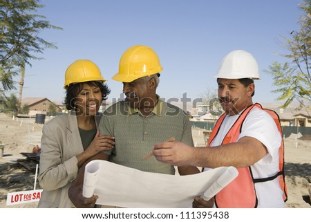 Architect with blueprint discussing at construction site - stock photo