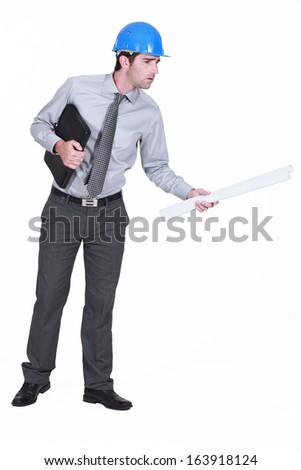 architect with briefcase holding blue prints looking concerned - stock photo