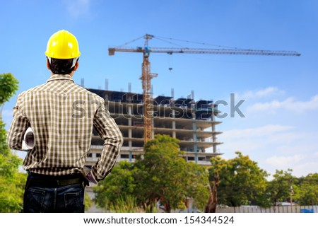 architect with holding blueprints looking at the blurred construction background in blue sky
