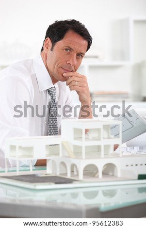 Architect with plans and 3D model - stock photo