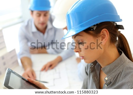 Architect with security helmet using electronic tablet