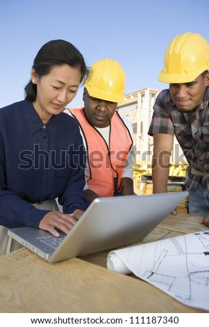Architect with workers using laptop at construction site - stock photo