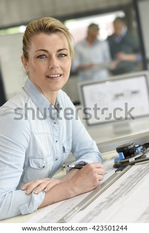 Architect woman working on drawing table