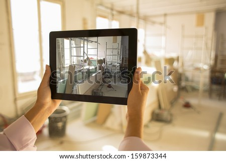 Architect woman working with electronic tablet, takes a picture - stock photo