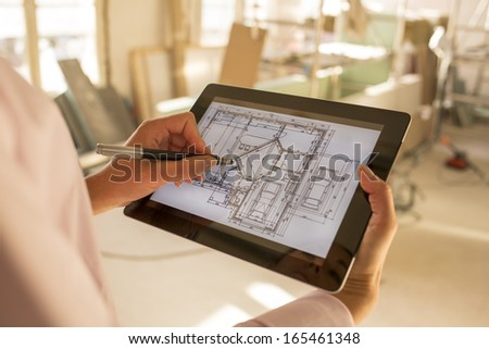 Architect woman working with stylus on electronic tablet - stock photo