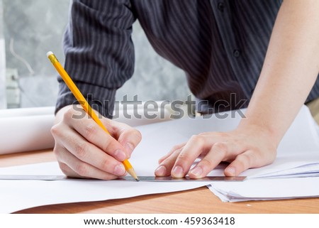 architect working and sketching architectural drawing plan on table in office