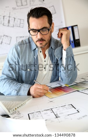 Architect working in office on blueprint - stock photo