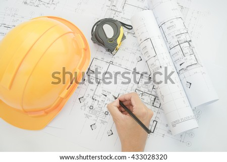 Architect working on construction blueprint. Architects workplace - architectural project, blueprints, helmet, measuring tape, Construction concept. Engineering tools. Top view - stock photo