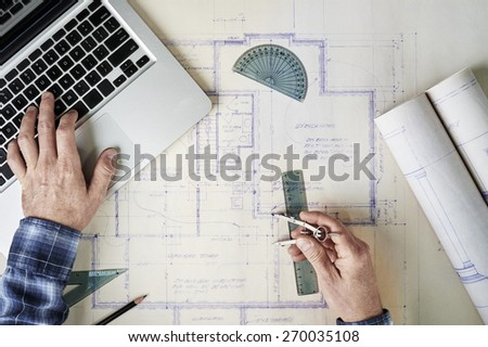 Architect working with blueprints and a computer - stock photo