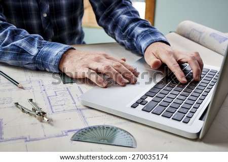 Architect working with blueprints and a computer