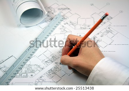 Architect working with blueprints.  Workspace includes rolled blueprints and architect ruler. - stock photo