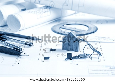 Architect workplace with blueprints, tools and house key - stock photo