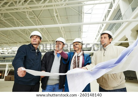 Architects and engineer workers with blueprints inside building under construction - stock photo