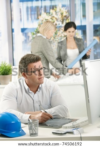 Architects concentrating on work, designer drawing at table, colleagues discussing plans in background.? - stock photo