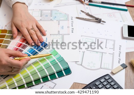 architects hands working with drawing sketch home, color sample and other working tools - stock photo