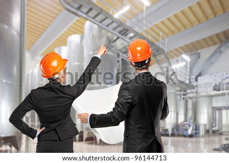 Architects holding blueprints and looking in a construction site - stock photo