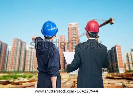 architects looking at blueprint in front of construction site - stock photo