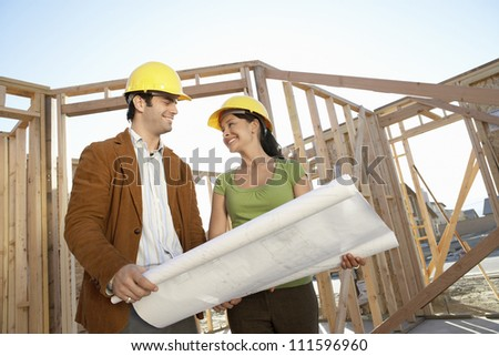 Architects looking at each other while holding blueprint at construction site - stock photo