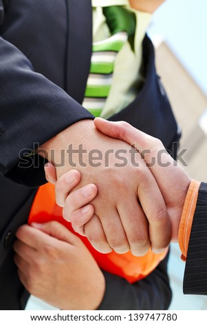 Architects shaking hands at construction site - stock photo