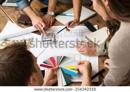 Architects team discussion on blueprints in office - stock photo