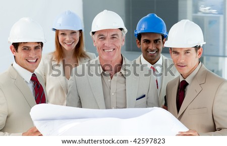 Architects with hardhats in a building site smiling at the camera - stock photo
