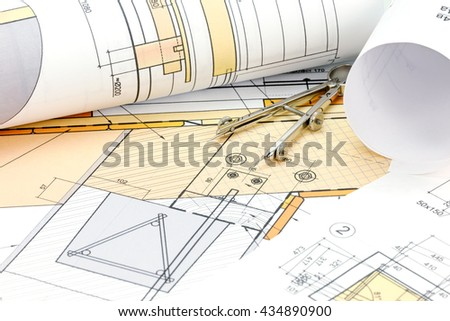 architects workspace with blueprint, rolls and drawing compass - stock photo