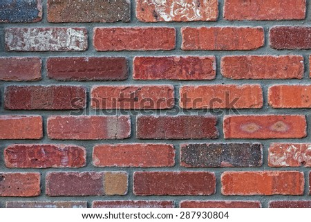Architectural background close up detail of precision masonry brick wall. Weathered bricks of different colors with most in the burgundy to red range. Gray cement. Horizontal format.