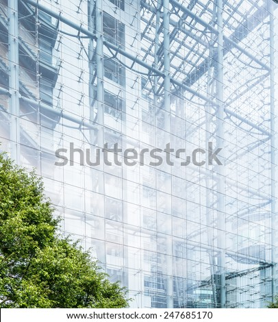 Architectural background of a modern high-rise building with a clear glass facade and view through to the staircases between floors forming a parallel pattern - stock photo