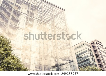 Architectural background of a modern high-rise building with a clear glass facade and view through to the staircases between floors forming a parallel pattern