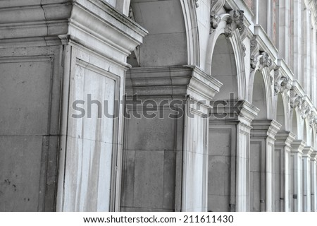 Architectural background of a row of classical rectangular columns in a colonnade supporting a row of arches, receding perspective