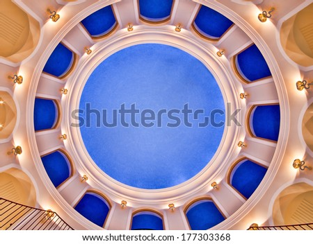 Architectural background of a striking circular blue domed ceiling with radial arches on two floors viewed from directly below - stock photo