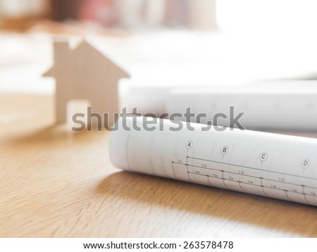 Architectural blueprint for construction over blurred home model - stock photo