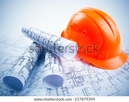 Architectural blueprint rols and helmet - stock photo