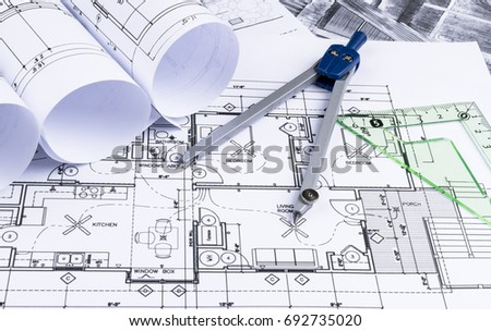 Architectural Blueprints And Blueprint Rolls And A Drawing Instruments On  The Worktable. Drawing Compass,