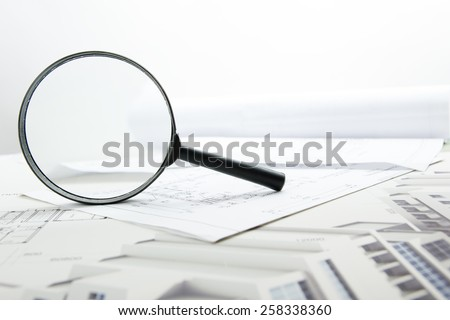 Architectural blueprints and blueprint rolls with magnifying glass. - stock photo